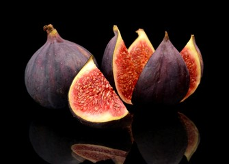Three figs split like flower isolated on black background