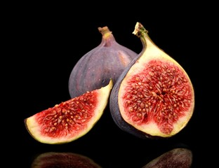 Three sliced figs isolated on black background