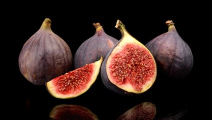 Group sliced figs isolated on black background