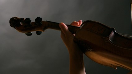Woman playing violin over dark background. 4K, UHD
