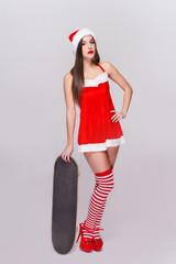 Sexy santa woman posing with skateboard