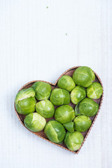 heart shape with fresh green broccoli on white table
