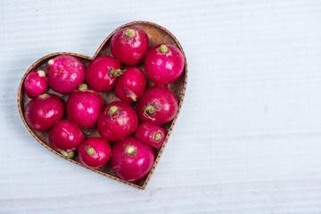 heart shape with fresh radish on white table