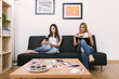 two young women with a smartphone and a book at home