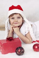 Happy girl in Santa's hat celebrating Christmas