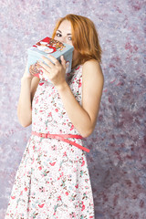 Beautiful red-haired girl with gift box in hands.