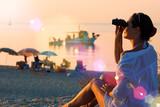 Girl with binoculars on the coast
