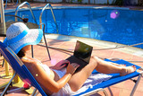 Young Woman sunbathing on deckchair with laptop