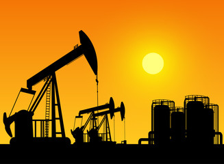 silhouette of working oil pumps on sunset background