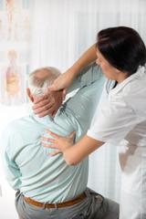 Chiropractic: Chiropractor examining senior man at office