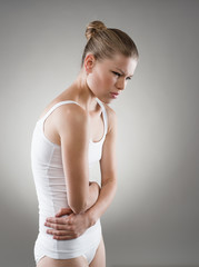 Abdomen pain. Young woman touching her abdomen in pain