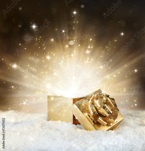 magic shining of christmas gift - golden stardust and snow - 73675032