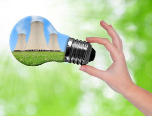 Hand holding bulb with nuclear power plant