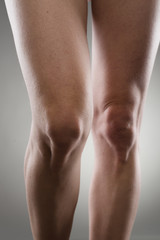 Healthy female legs over grey. Knee joint care concept.