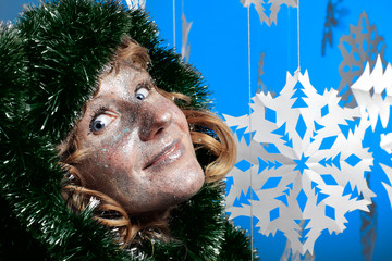Young woman in Christmas tree decorations and glistering make up
