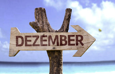 December (In German) sign with a beach on background