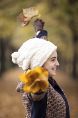 Beautiful young woman with autumn leaves in hands at the park