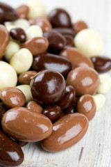 chocolate covered nuts and raisins on wooden surface