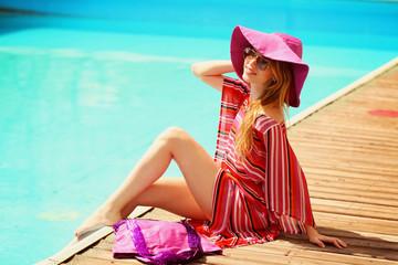 Beautiful young woman lying on sun lounger near pool.