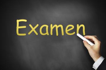 Hand schreibt Examen auf schwarze Tafel