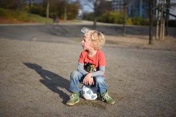 Kleiner Junge spielt auf dem Spielplatz Fußball