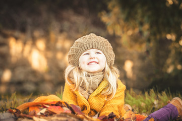 Beautiful girl, smiling blonde plays with the autumn leaves