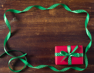Red gift box with green ribbon lying on the wooden background