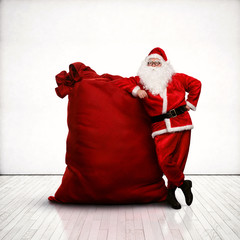 Santa Claus leaning on huge red sack