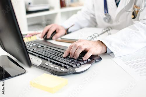 Leinwanddruck Bild Doctor typing on a computer keyboard