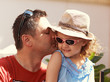 Loving father kissing his happy child girl in sun glasses