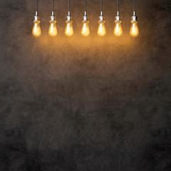 Decorative vintage lightbulbs on dark concrete background