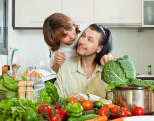 Positive couple preparing vegetable salad