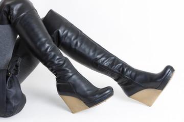 detail of sitting woman wearing platform black boots