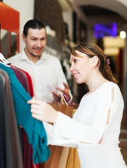 couple choosing clothes at shop