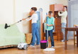 Couple with son vacuuming together