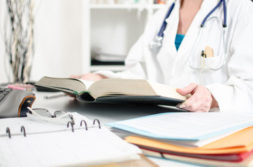 Female doctor reading a medical book