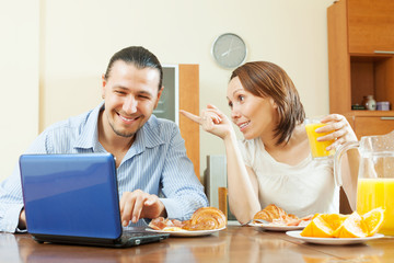 Happy couple looking e-mail in laptop during breakfast