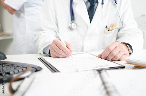 Fototapeta Doctor signing a medical report