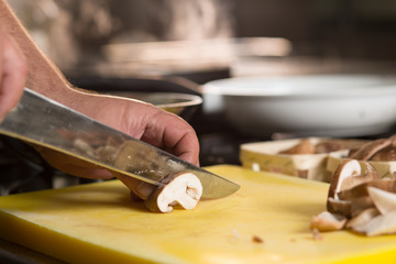 Male chef slicing brown mushroom on a yellow chopping boards