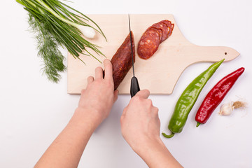 Female cutting slices of red sausage on a wooden chopping board