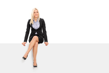 Businesswoman sitting on a blank billboard