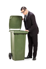 Businessman looking into a trash can