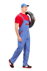 Mechanic carrying a tire and walking