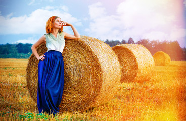beautiful red-haired girl near the haystack