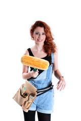 Junge hübsche Heimwerkerin mit Farb Roller lächelt