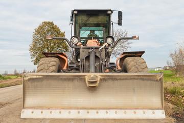 Strassenbau - Ein grosser oranger Grader - Frontansicht