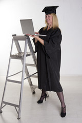 Graduate in cap and gown in the workplace using laptop