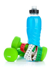 Two green dumbells, tape measure and drink bottle. Fitness and h
