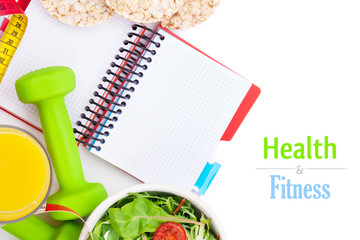 Dumbells, tape measure, healthy food and notepad for copy space.