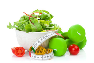 Two green dumbells, tape measure and healthy food. Fitness and h